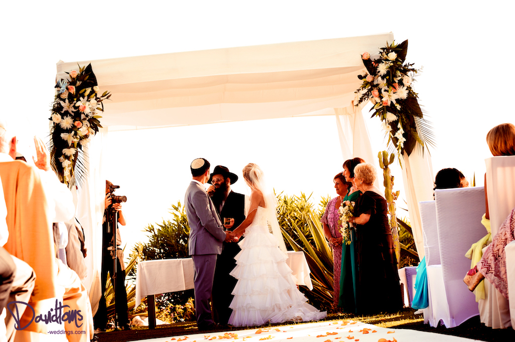 Bride and groom under the chuppah over looking the mediterranean sea