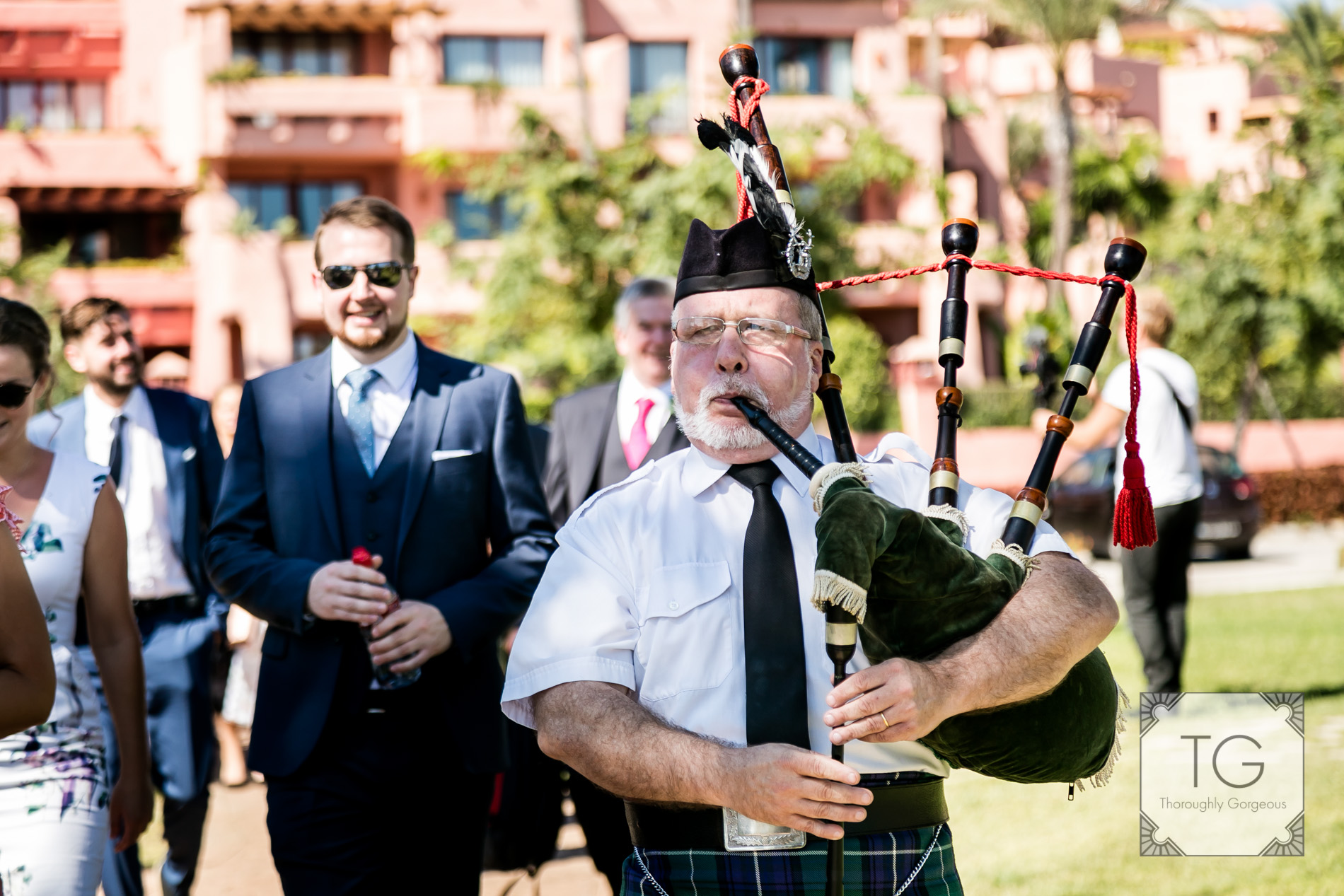 Scottish piper leads weddings guests to beach