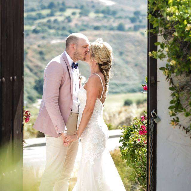 The bride and groom kiss in the beautiful Hacienda
