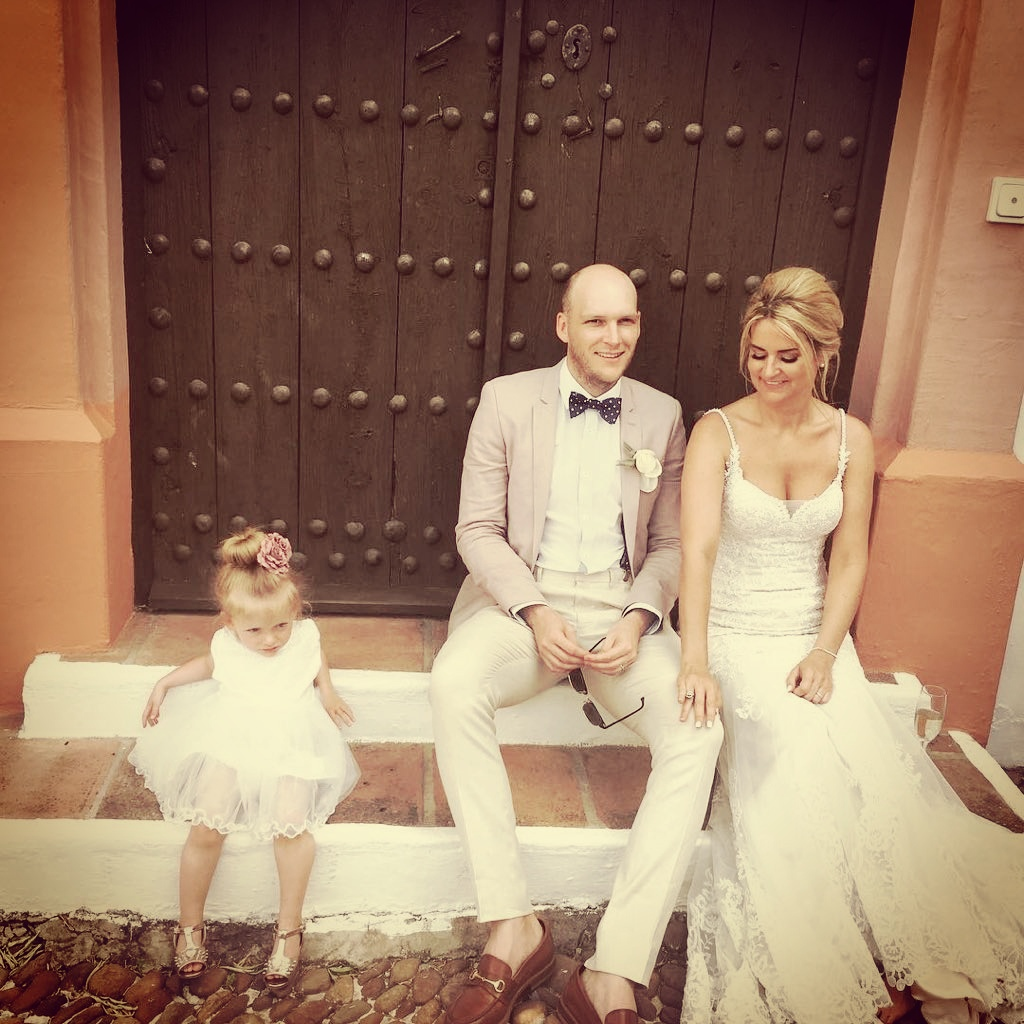 Bride, groom and bridesmaid taking a quiet moment at the steps of the Hacienda.
