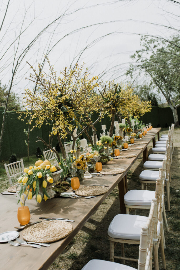 Natural arboreal archways frame the beautiful floral table decorations of the wedding breakfast