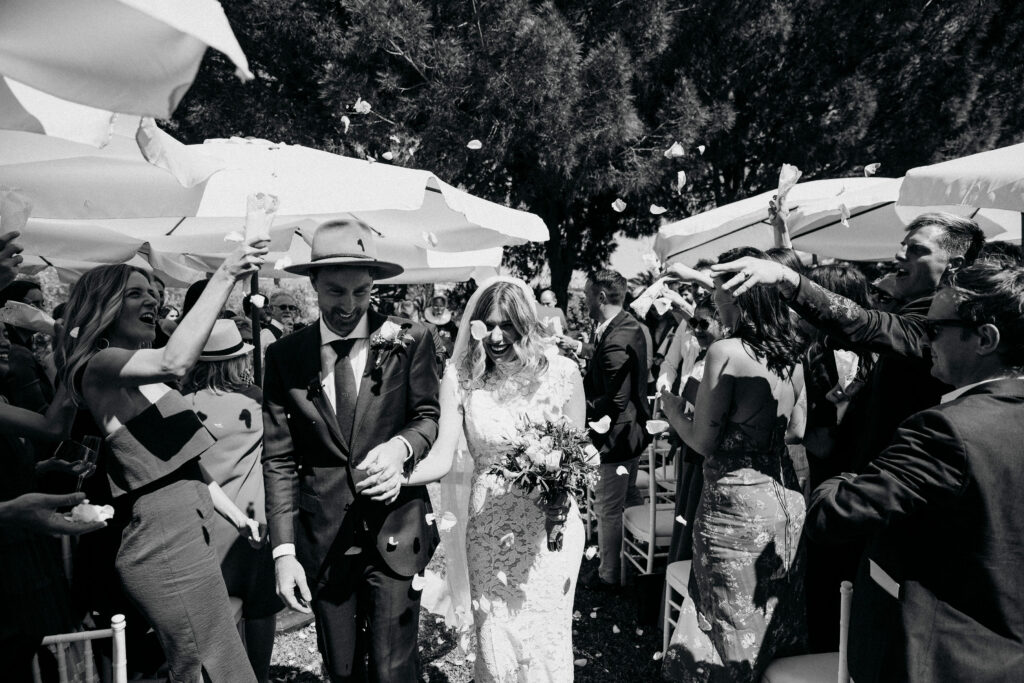 The bride and groom are showered with confetti by their family and friends - photo by @simon_gorges