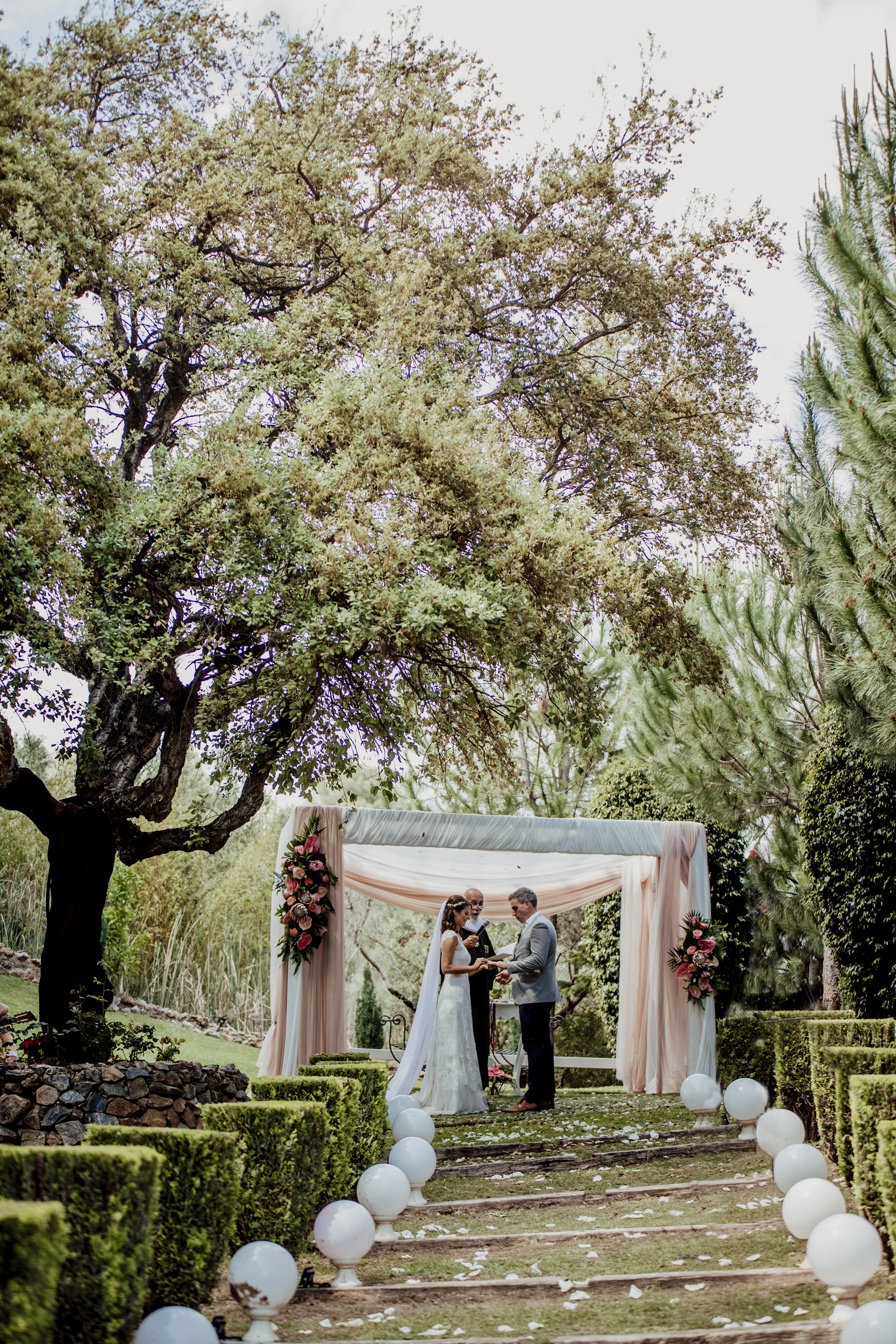 The bride and groom exchanging their vows in the villa's stunning gardens