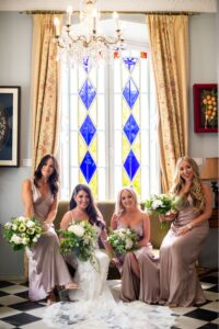 The beautiful bride and her beautiful bridesmaids in front of the stunning stained glass windows of the Hacienda - Jeremy Standley Photographer