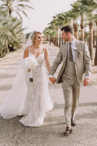 The bride and groom outside the Finca's grounds which are flanked by elegant palm trees