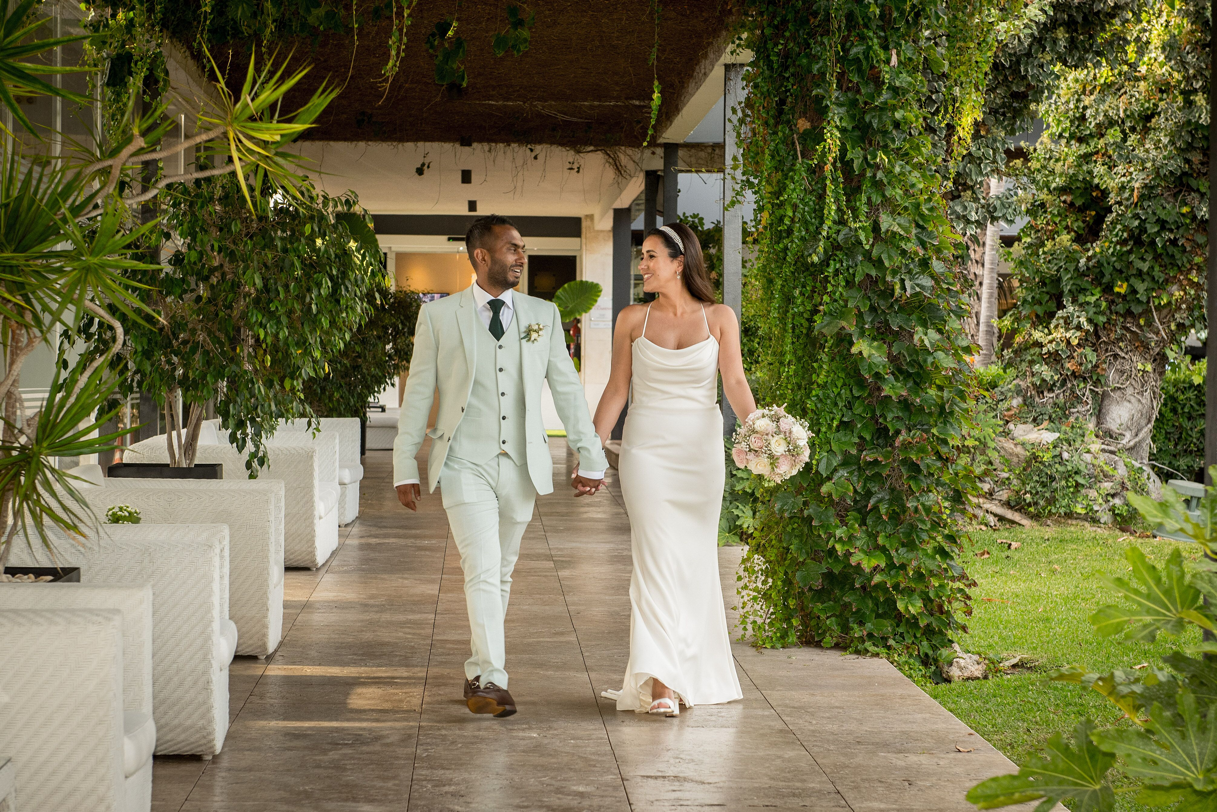 The bride and groom strolling through the hotel grounds