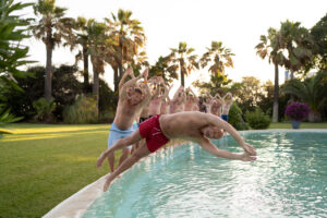 The groom and some of the male guests putting on a diving display at the pool - Chris Wallace, Carpe Diem Photography