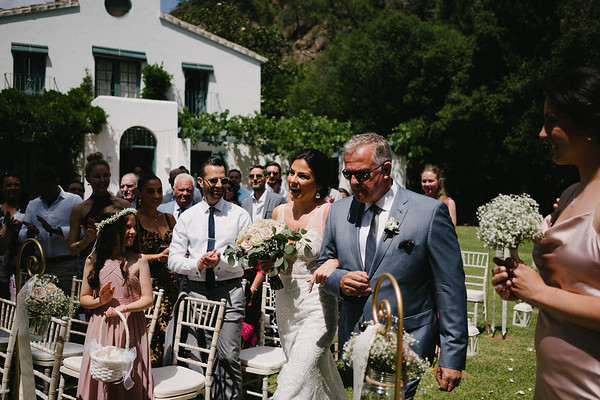 The bride and her father make their way down the aisle on the lawns of the Villa - Image Pedro Bellido Photograhy