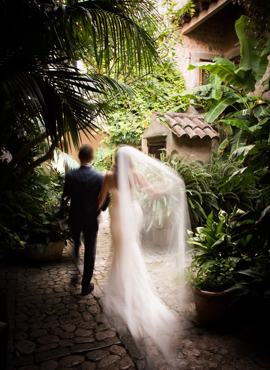 The newlyweds walk through the tropical garden of their dream wedding venue in Spain.