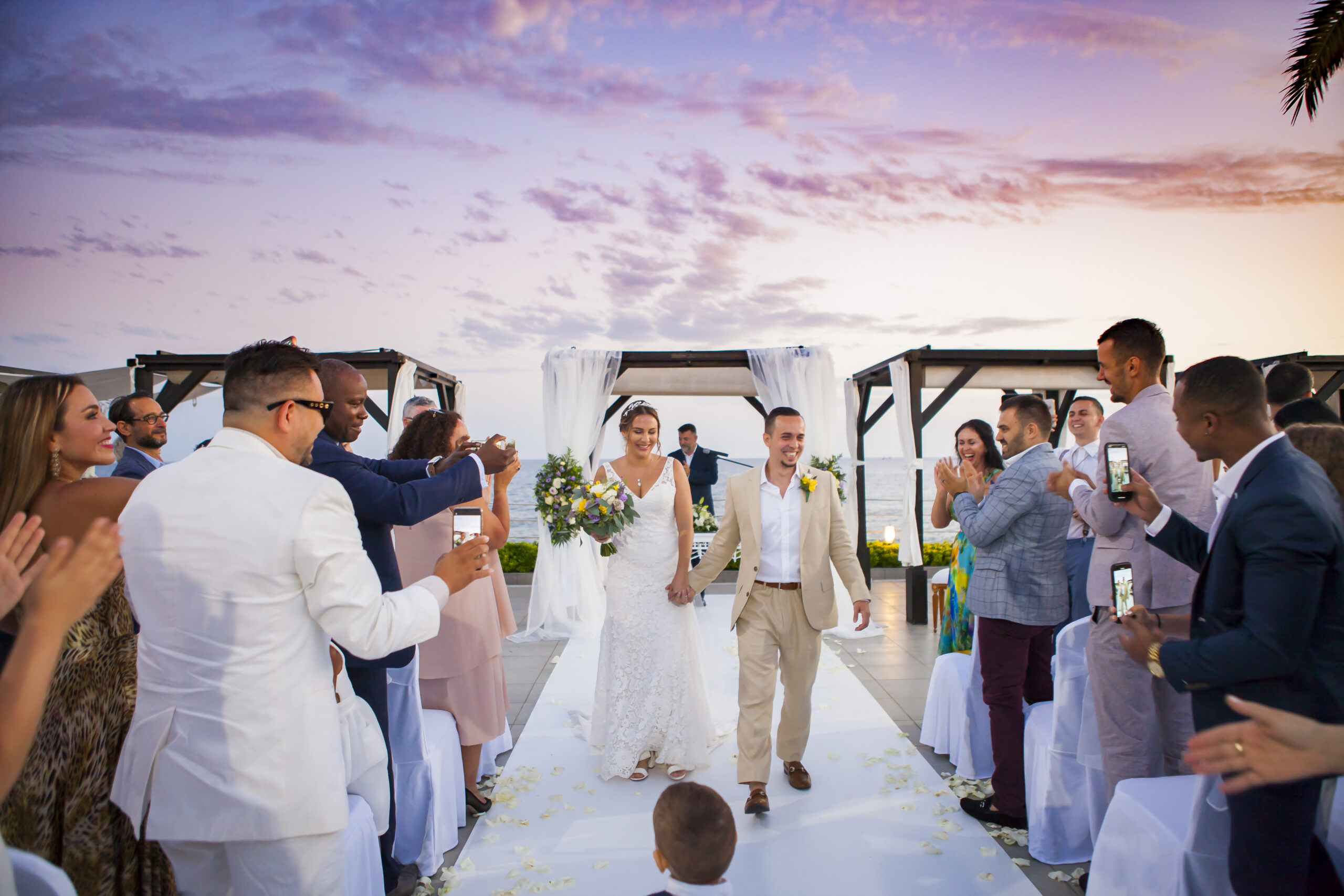 The bride and groom walking back down the aisle to the delight of their family and friends after the beach club ceremony