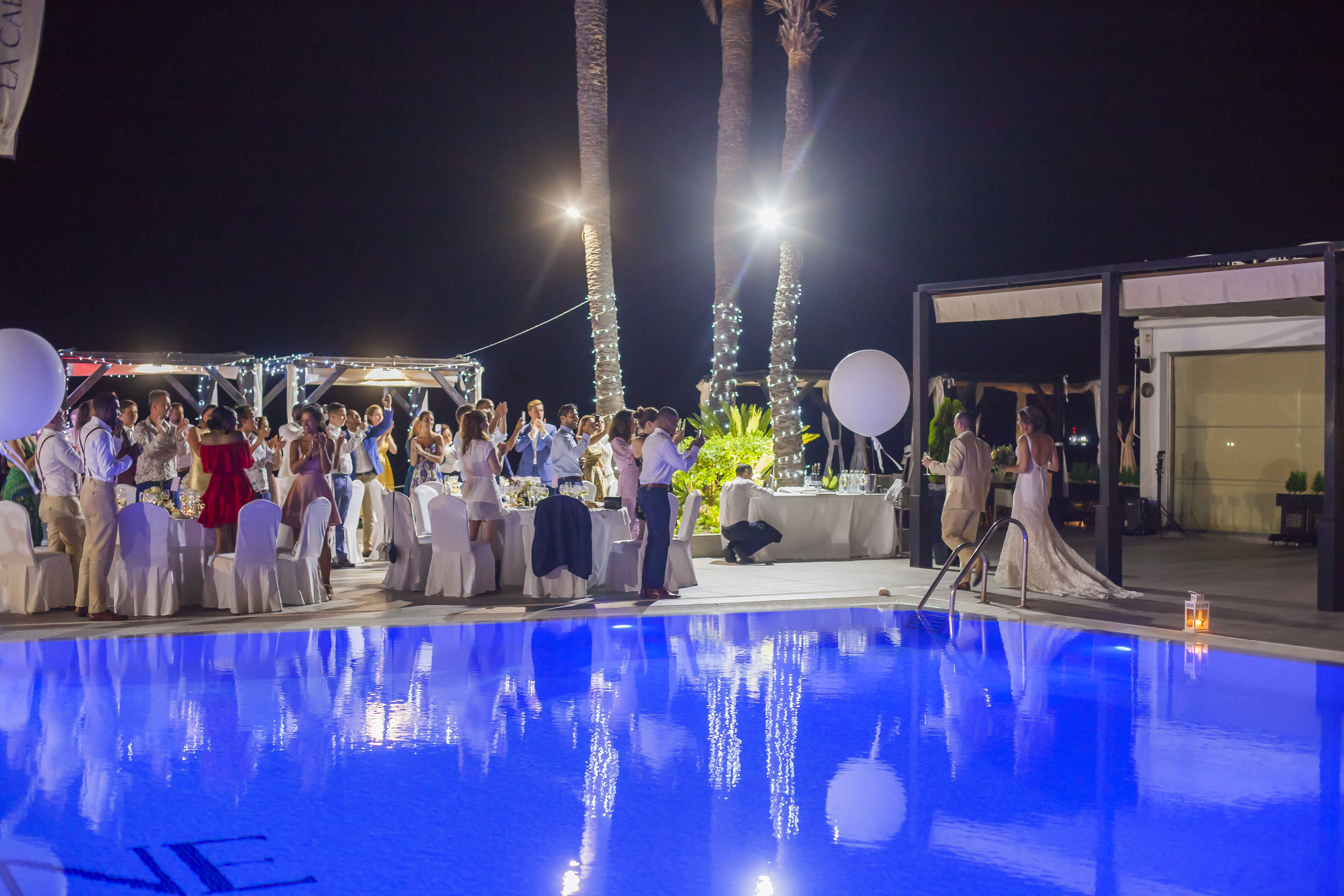 The bridal party and the gorgeous pool area illuminated at night