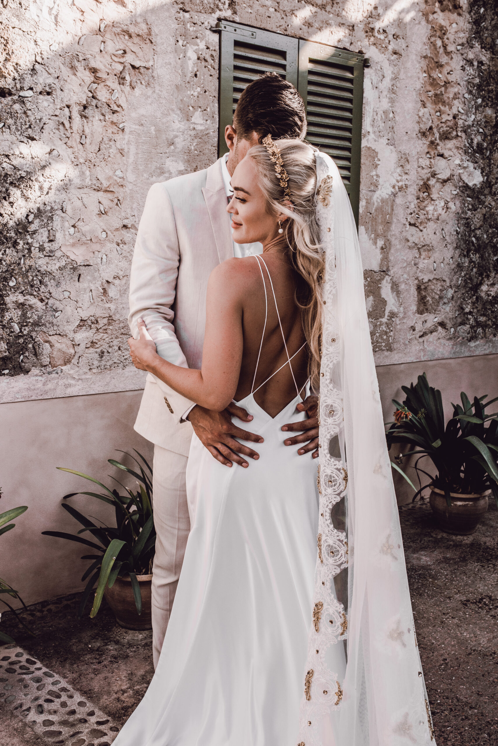 The bride and groom share a moment outside the charming Finca - Rebecca Jackson Photography