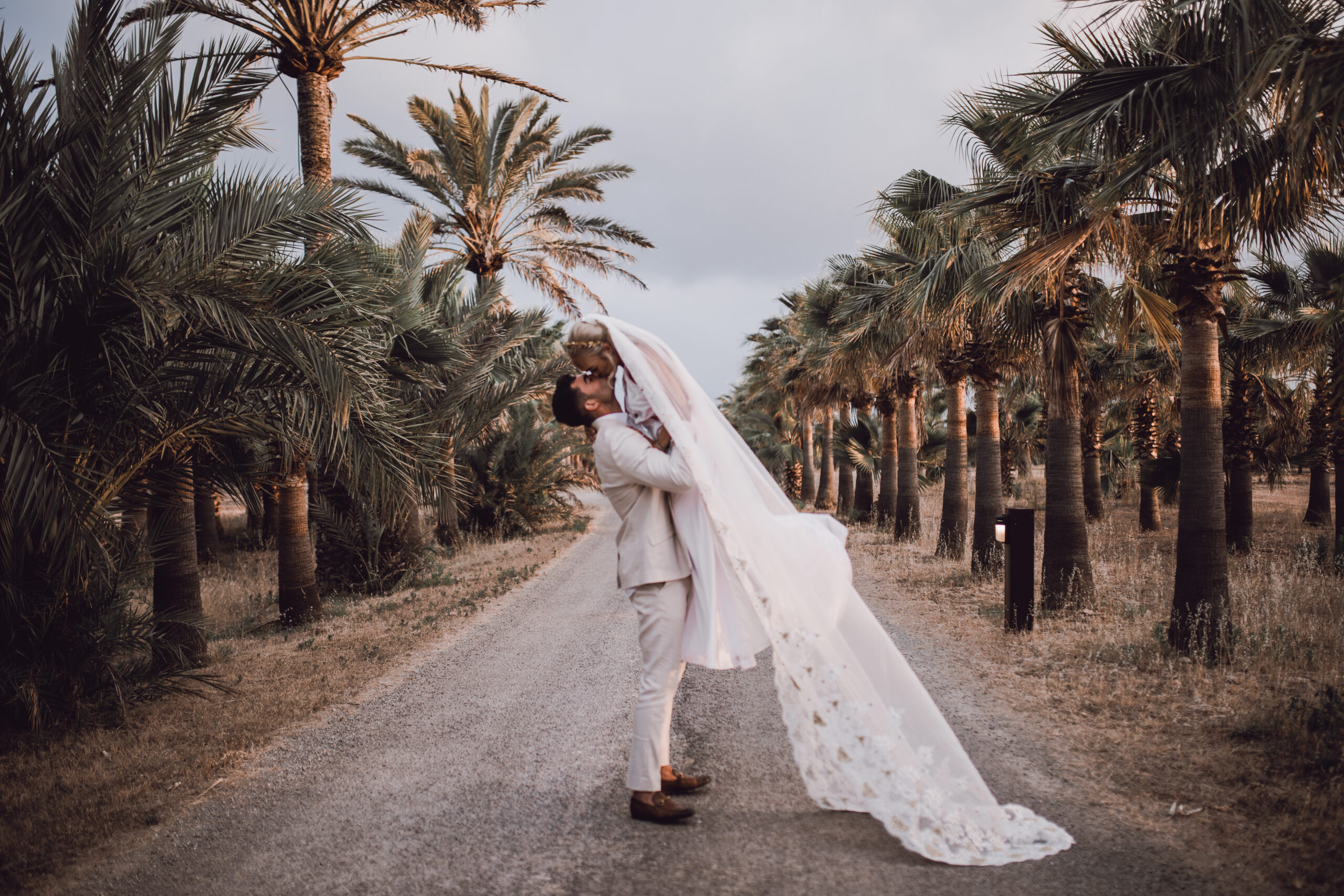 The groom lifts his bride on the sweeping driveway of the Finca - Rebecca Jackson Photography