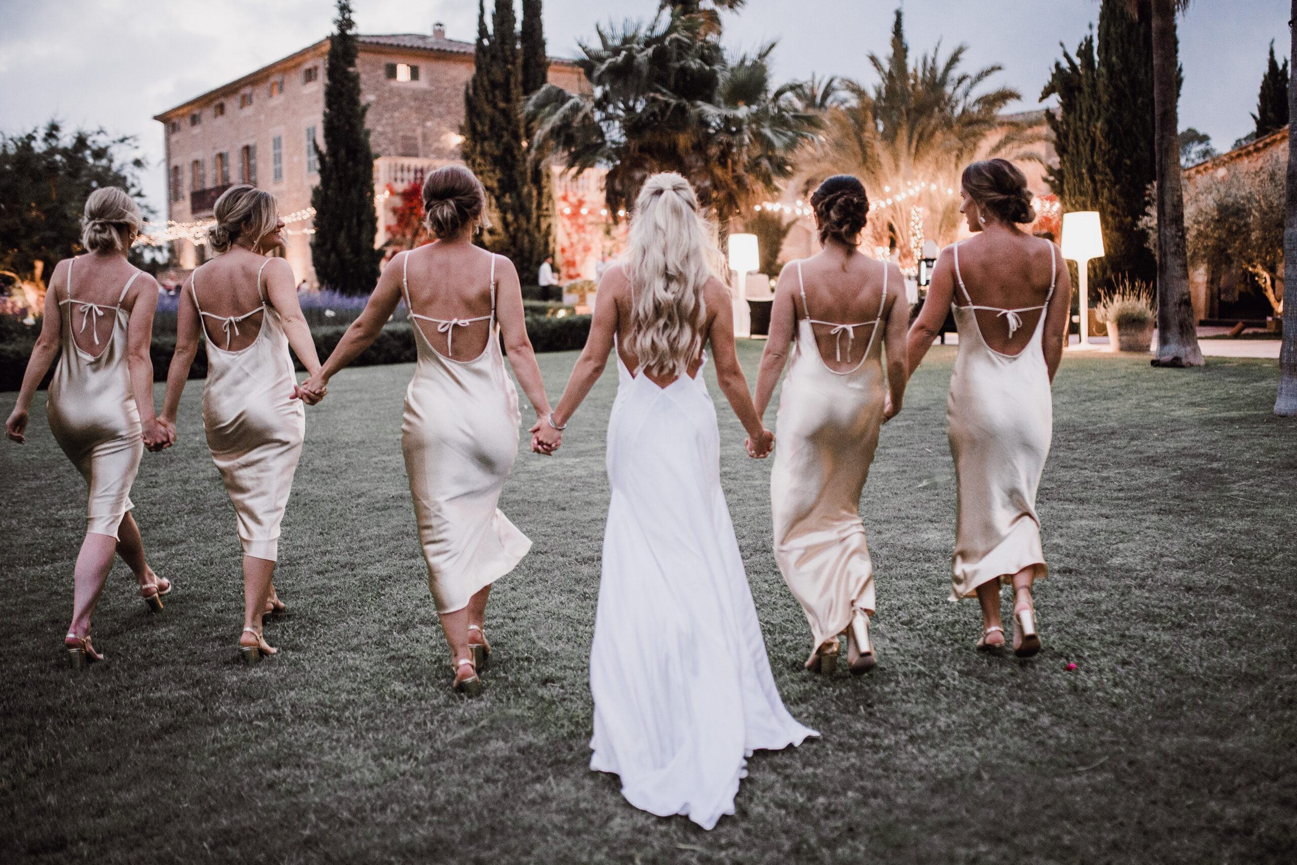 The bride and her bridesmaids walking hand in hand across the Finca's lawns - Rebecca Jackson Photography