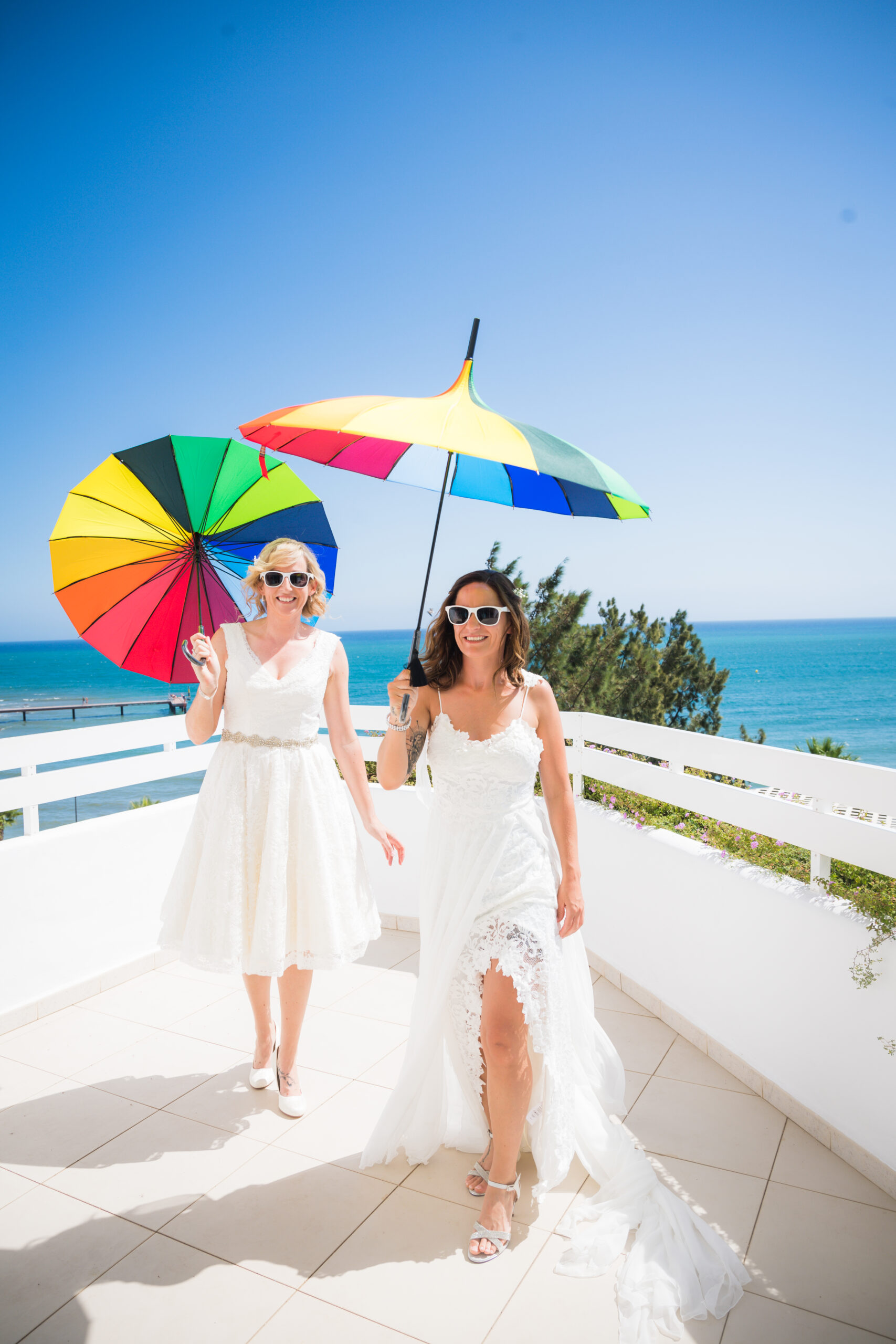 The happy couple in shades under rainbow parasols next to the Mediterranean Sea - Rebecca Davidson Photography