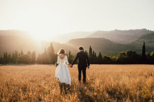 Bride and groom walking in fields - Roger Castellvi