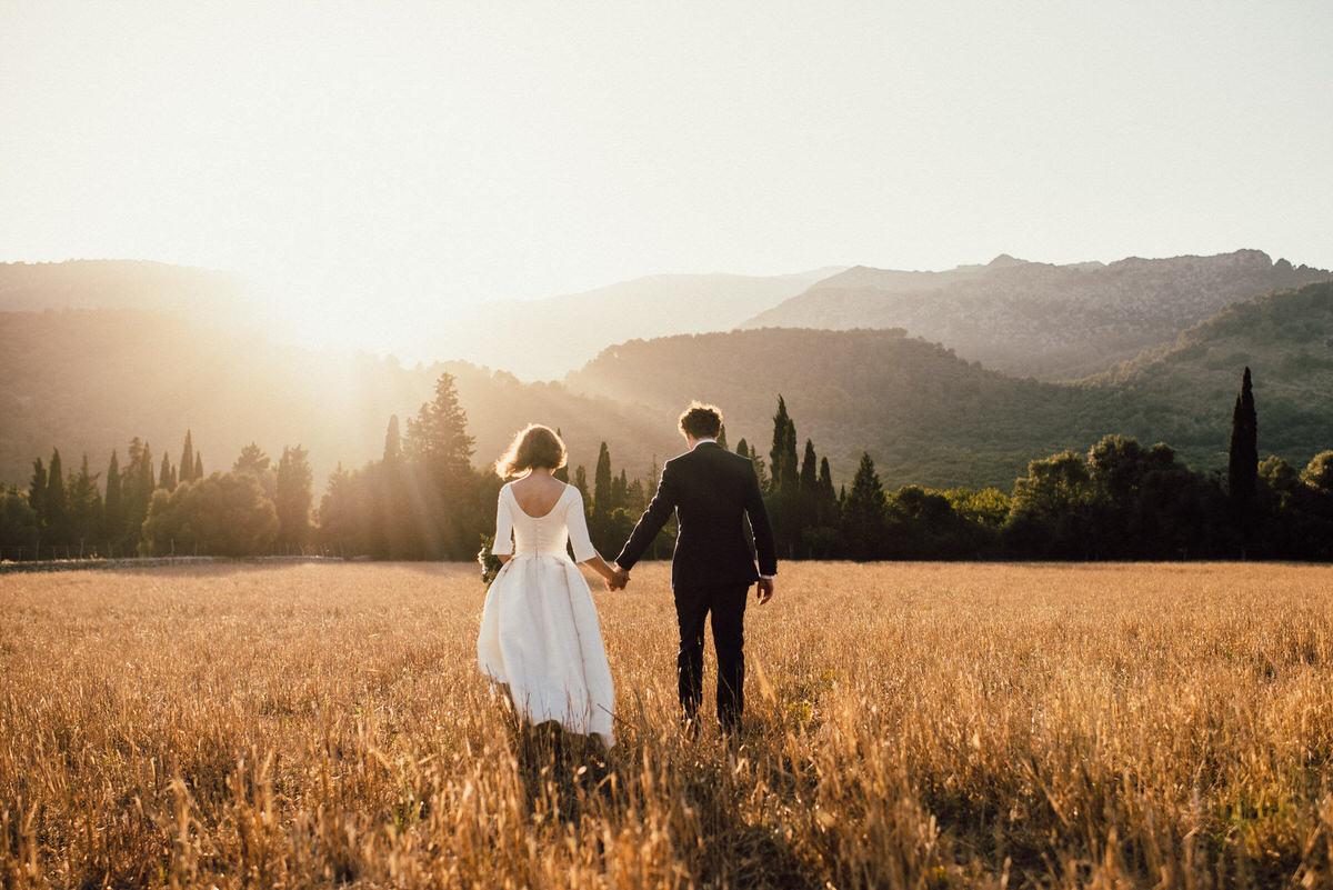 Bride and groom walking in fields - Roger Castellvi