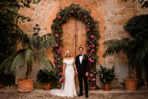 Bride, groom and stunning floral archway - Roger Castellvi