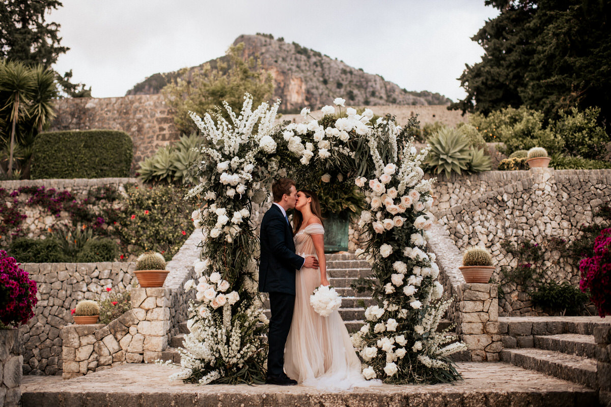 Bride and groom kiss in beautiful gardens - Roger Castellvi