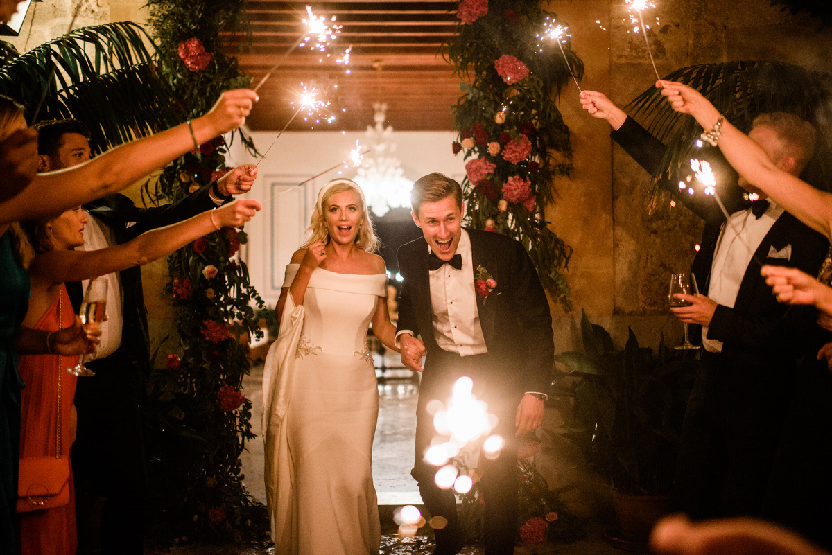 Bride and groom walking through an archway of sparklers - Roger Castellvi