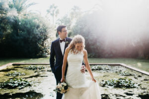 Bride and groom and the wedding venue's magnificent pond - Roger Castellvi