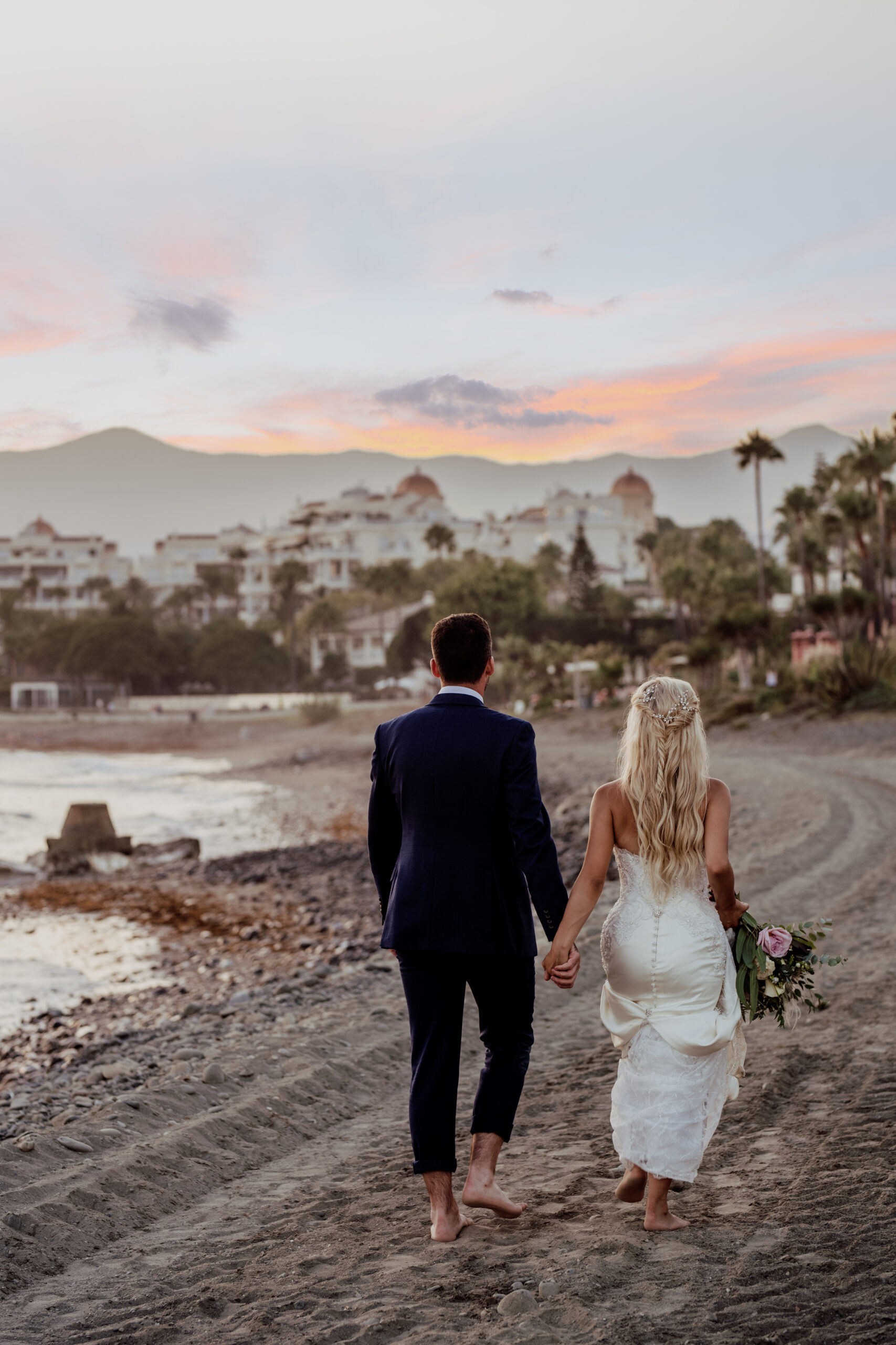 The bride and groom stroll on the beach at sundown - Rebecca Davidson Photography