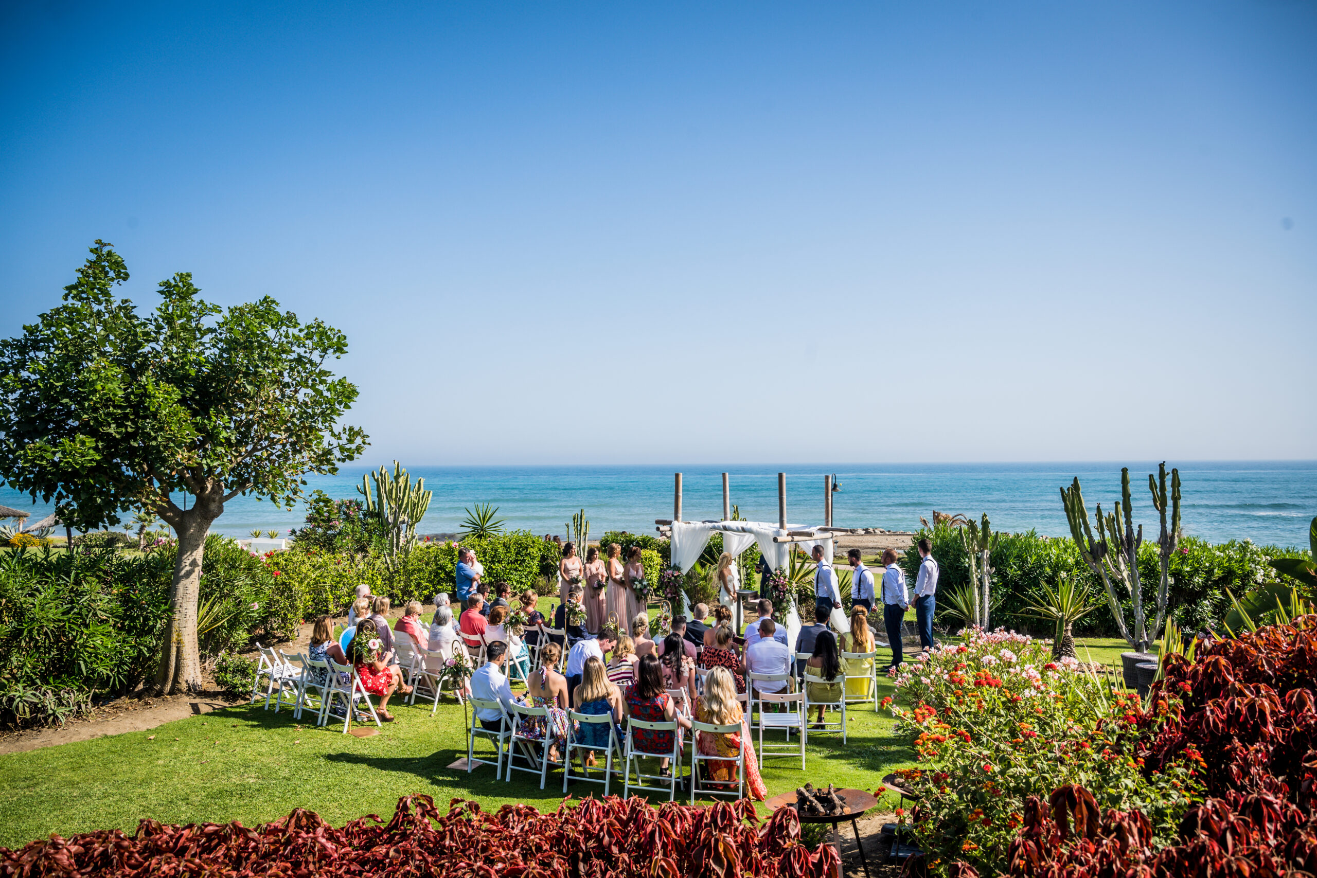 The wedding ceremony in the grounds of the beach club - Rebecca Davidson Photography