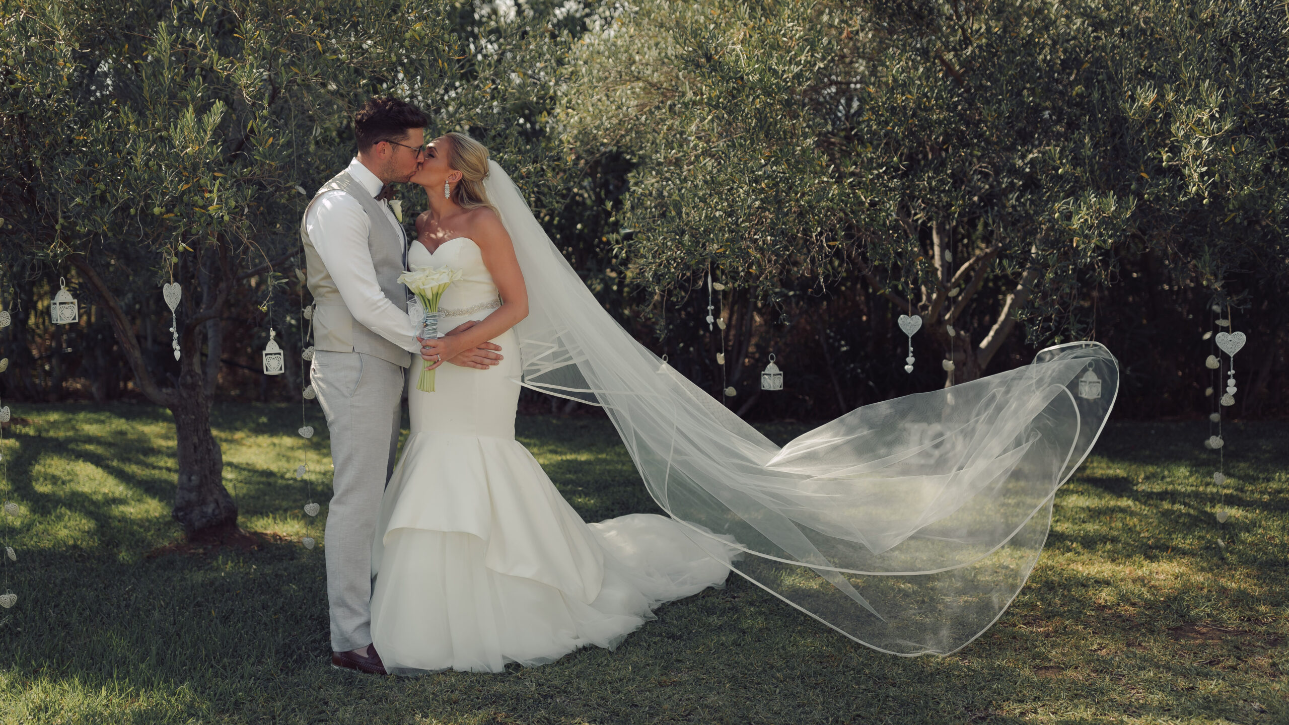 The bride and groom share a kiss in the grounds of the Hacienda - Hove & Co Photography