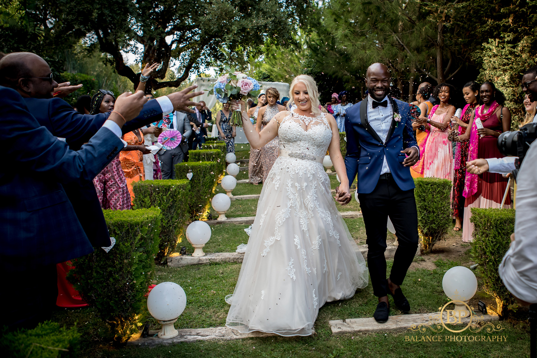 The newlyweds walking back down the aisle to greet their guests - Balance Photography